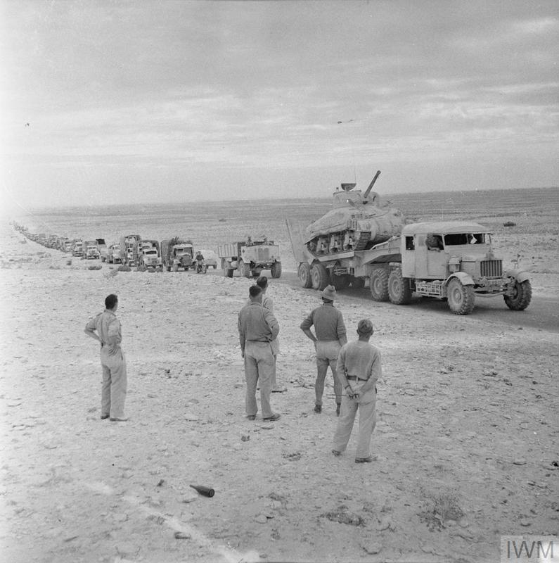 A long line of transport, including a Sherman tank on a Scammell tank transporter, moving along the coast road in pursuit of the enemy, 11 Nov 1942. IWM photo E 19296.