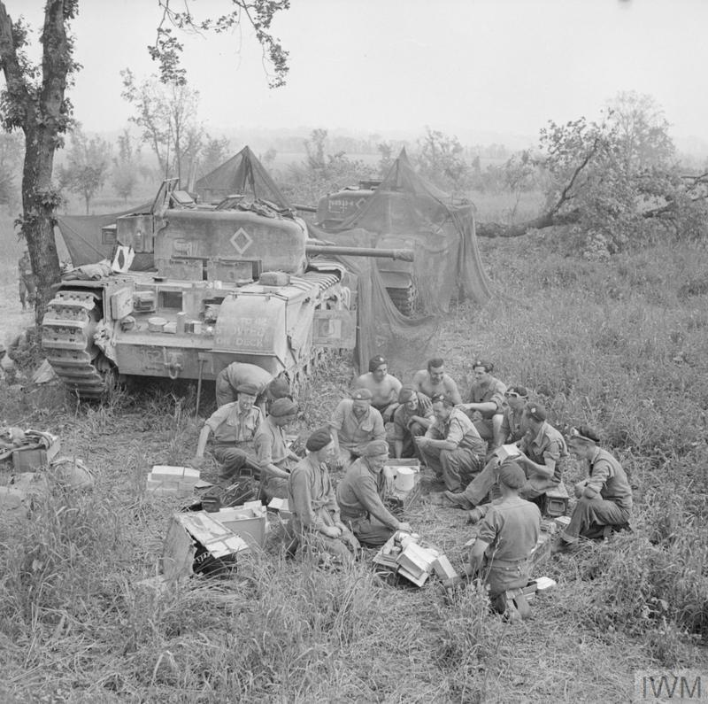 Churchill tank crews HQ Troop, 51st Royal Tank Regiment, 25th Tank Brigade, share out rations near their camouflaged vehicles before going into action in support of 1st Canadian Division. Italy, 17 May 1944. IWM photo NA 14976.