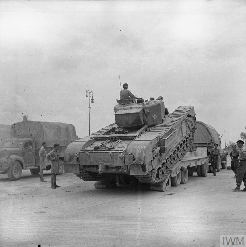 A new Churchill tank being unloaded from a transporter. Arezzo, Italy, 19 Jul 1944. IWM photo NA 17040.