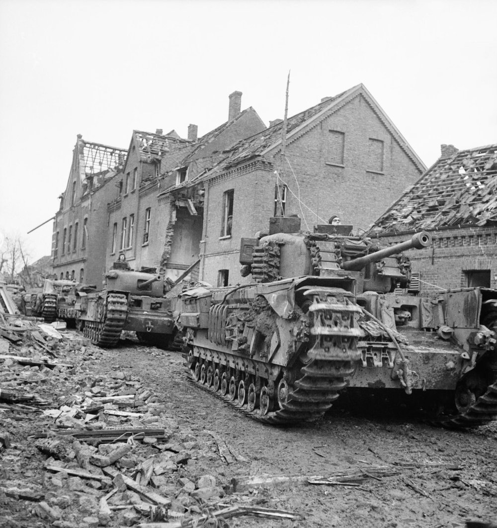 A column of Churchill tanks move along a devastated street in the town of Kleve, Germany, 12 Feb 1945. IWM photo B 14513.