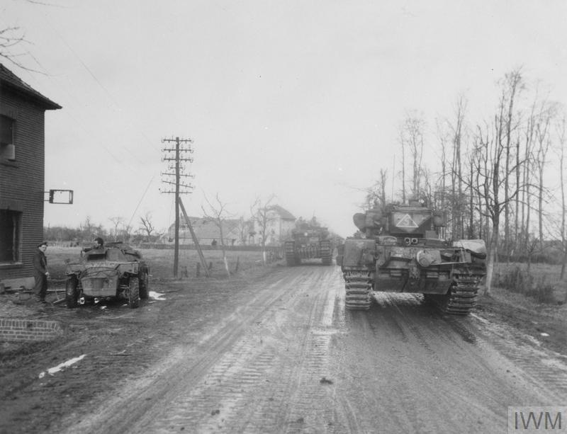 Churchill tanks of 34th Tank Brigade north of Geilenkirchen, Germany, Dec 1944. The scout car on the left has the '156' unit serial indicating 107th Regiment RAC. IWM photo EA 47337.
