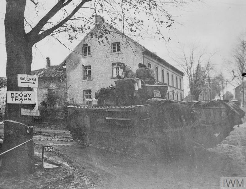 A Churchill tank of 147th Regiment, Royal Armoured Corps, 34th Tank Brigade, advances along a road near Geilenkirchen, Germany, Dec 1944. IWM photo EA 47338.