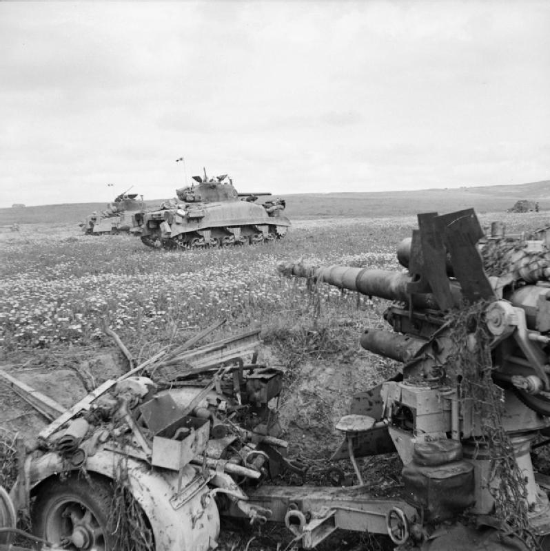 Sherman tanks advance past a knocked-out anti-tank gun of the type ''8.8-cm-PaK 36''. Tunisia, 23 Apr 1943. IWM photo NA 2321.