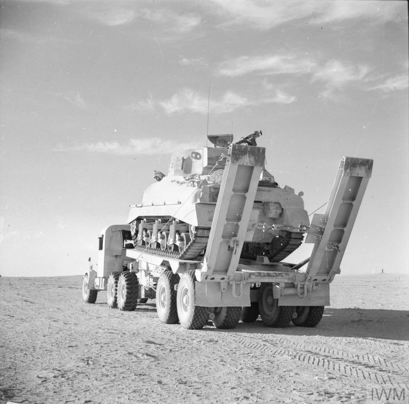 A Scammell Pioneer tank transporter carrying a damaged Sherman tank back to a REME repair workshop in the Western Desert, 29 Oct 1942. IWM photo E 18712.