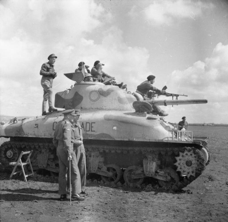 LTG W. G. Holmes, GOC 9th Army, stands on a Sherman tank of the Wiltshire Yeomanry to watch a gunnery display, 5 Apr 1943. IWM photo E 23451.