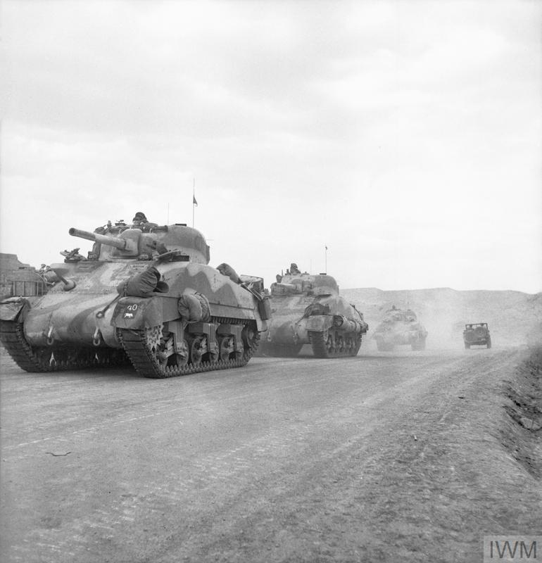 Sherman tanks of the Queen's Bays (2nd Dragoon Guards) advance through the Gabes Gap, 7 Apr 1943. IWM photo NA 1809.