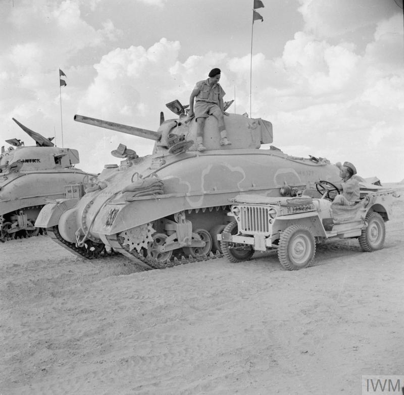 "A jeep and Sherman tanks of HQ 2nd Armoured Brigade, 10 Oct 1942. ""The white line on the tank was being used as a guideline by the Camouflage Unit who were called away before completing the painting of the Brigade's tanks."" IWM photo E 17898."