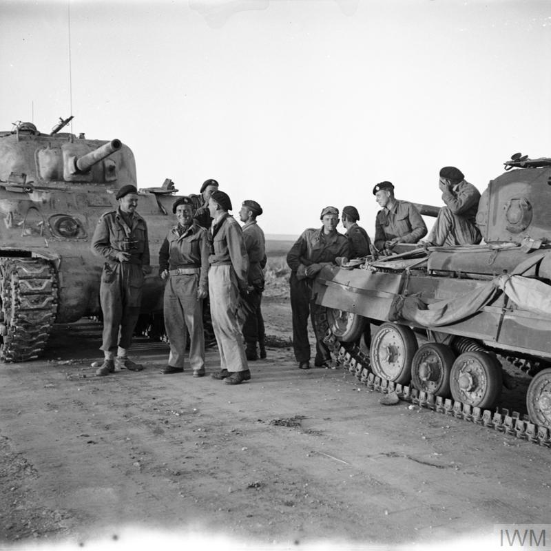 A Sherman tank crew greets a Valentine tank crew at the link-up of the First and Eighth Armies at Bou Ficha, Tunisia, 14 May 1943. IWM photo NA 2921.