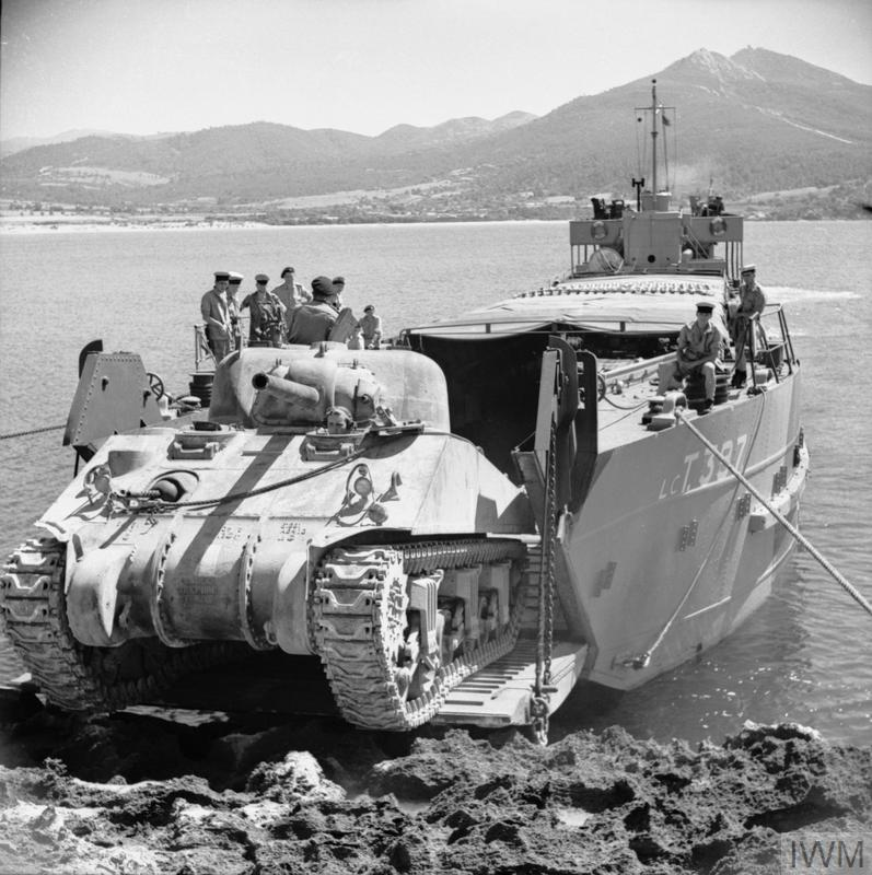 A Sherman tank leaves a landing craft during an exercise on the North African coast, 6 Jun 1943. IWM photo NA 3513.