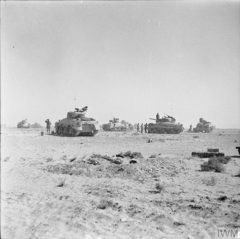Sherman tanks of 8th Armoured Brigade waiting just behind the forward positions near El Alamein before being called to join the battle, 27 Oct 1942. IWM photo E 18531.