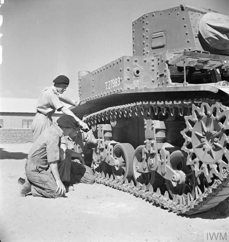 Men of the Royal Tank Regiment examining the tracks and suspension of the new American M3 Stuart tank at a training depot in Egypt, 17 Aug 1941. IWM photo E 3443E.