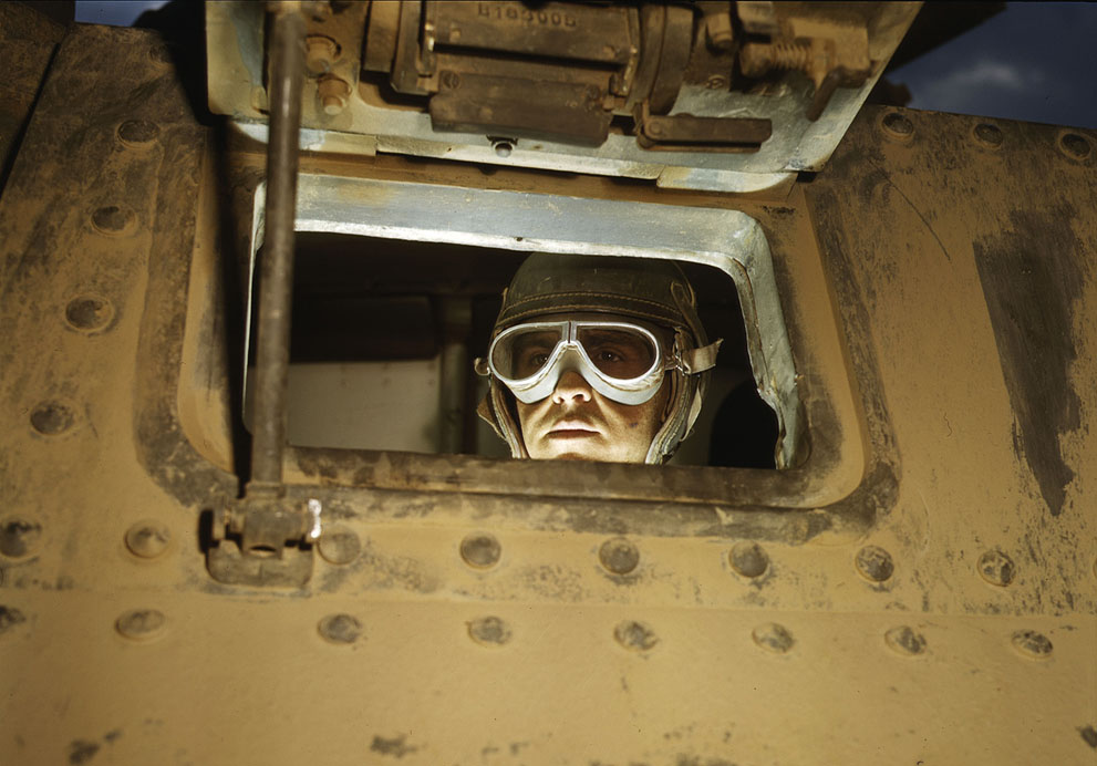 M3 medium tank driver looking through the forward port hole. Fort Knox, KY, Jun 1942.   Note: the white color on the interior of driver's hatch is from artificial light utilized for the photography session. Library of Congress photo.