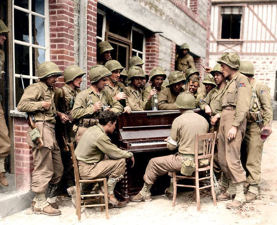 Soldiers from the 17th Armored Engineer Battalion, 2nd Armored Division gather round a piano for a sing-a-long in the Rue Monteglise, Barenton in Normandy. 10 AUG 1944.   Colorized by Jared Enos.