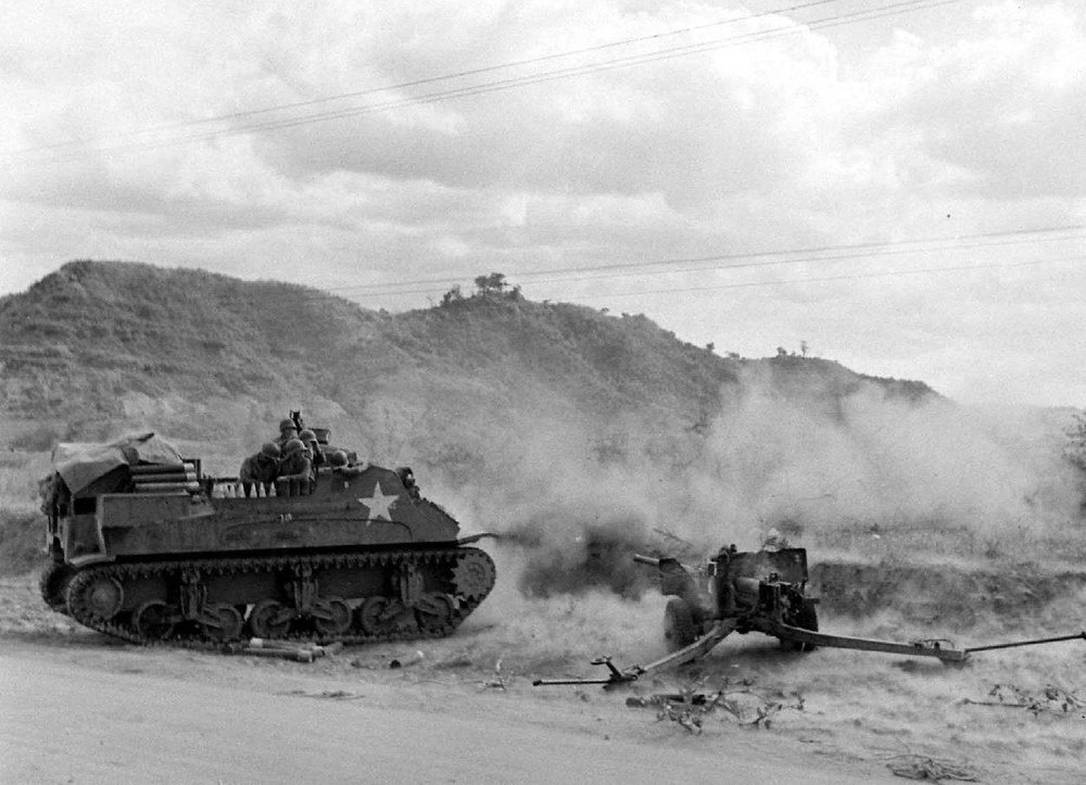 M7 Priest (Early Production) in full recoil. 57mm M1 anti-tank gun nearby.