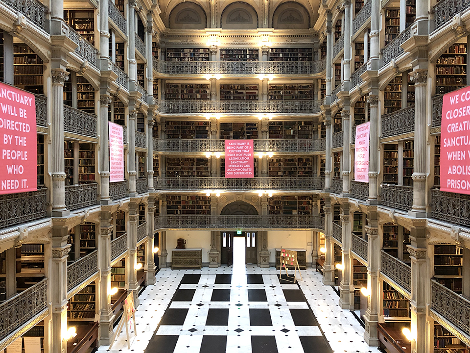 Interior of George Peabody Library with 5 pink banners
