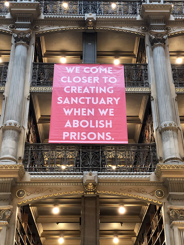 Pink banner at the George Peabody banner that reads: We come closer to creating sanctuary when we abolish prisons.