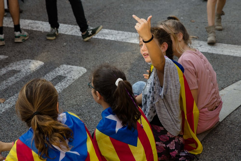 A young girl gives the middle finger to a police helicopter during a demonstration for Catalan Independence in Barcelona, Spain.
