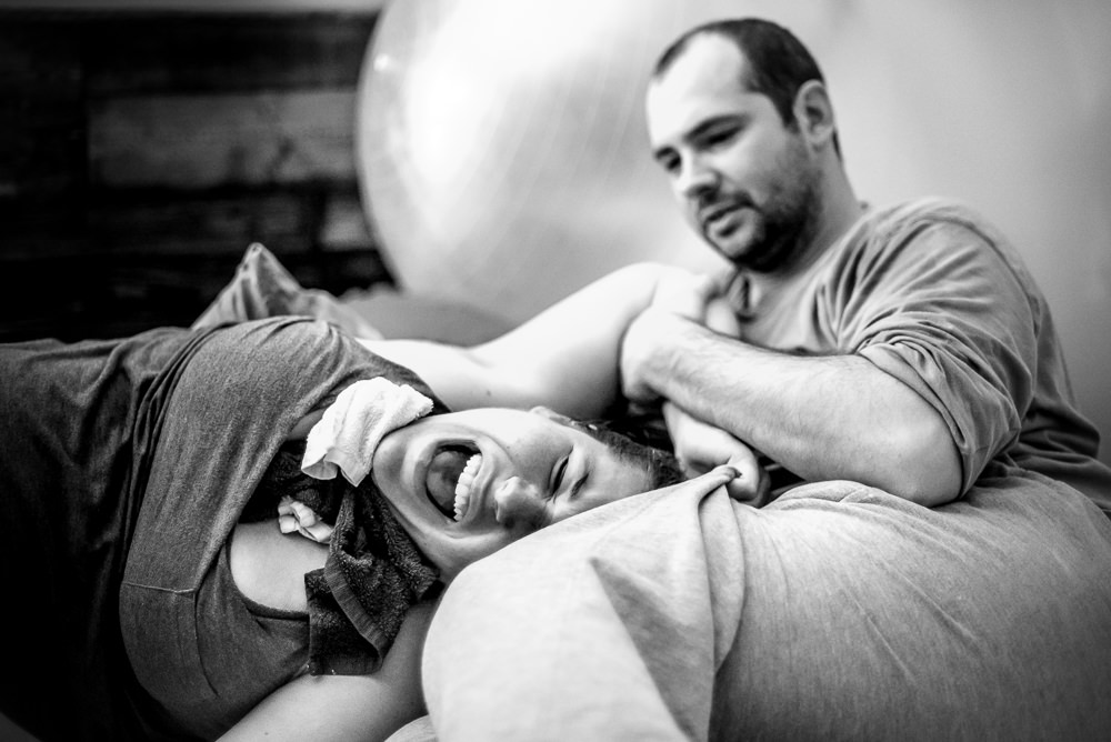 laboring mama needs the support of her husband as she moans through a hard contraction during her home birth in St. Louis.jpg