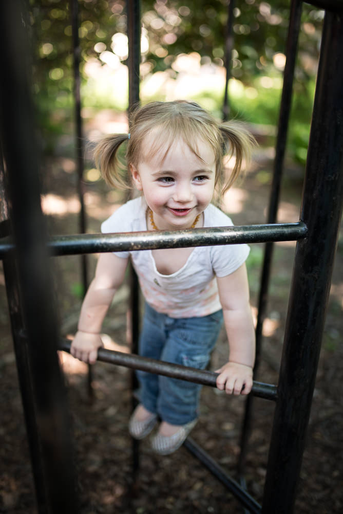 little sister climbs on playground during family documentary photo shoot.jpg