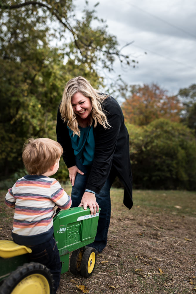 mom plays with son on a John Deere tractor during documentary photo session.jpg