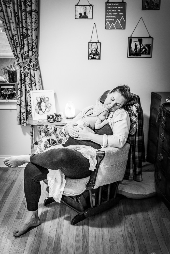 newborn baby snuggled against her mama in the rocking chair during a fresh 48 session in St. Louis, MO.jpg