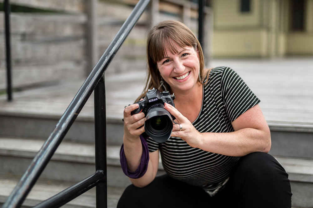 Dana-Jacobs-sits-on-stairs-with-her-trusty-camera-in-hand.JPG