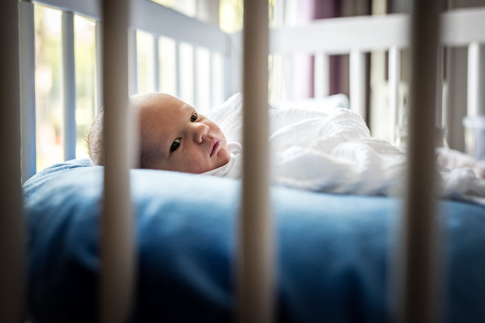 photo-of-newborn-baby-with-eyes-wide-open-shot-through-crib-slats-during-in-home-fresh-48-session-in-St-Louis-MO