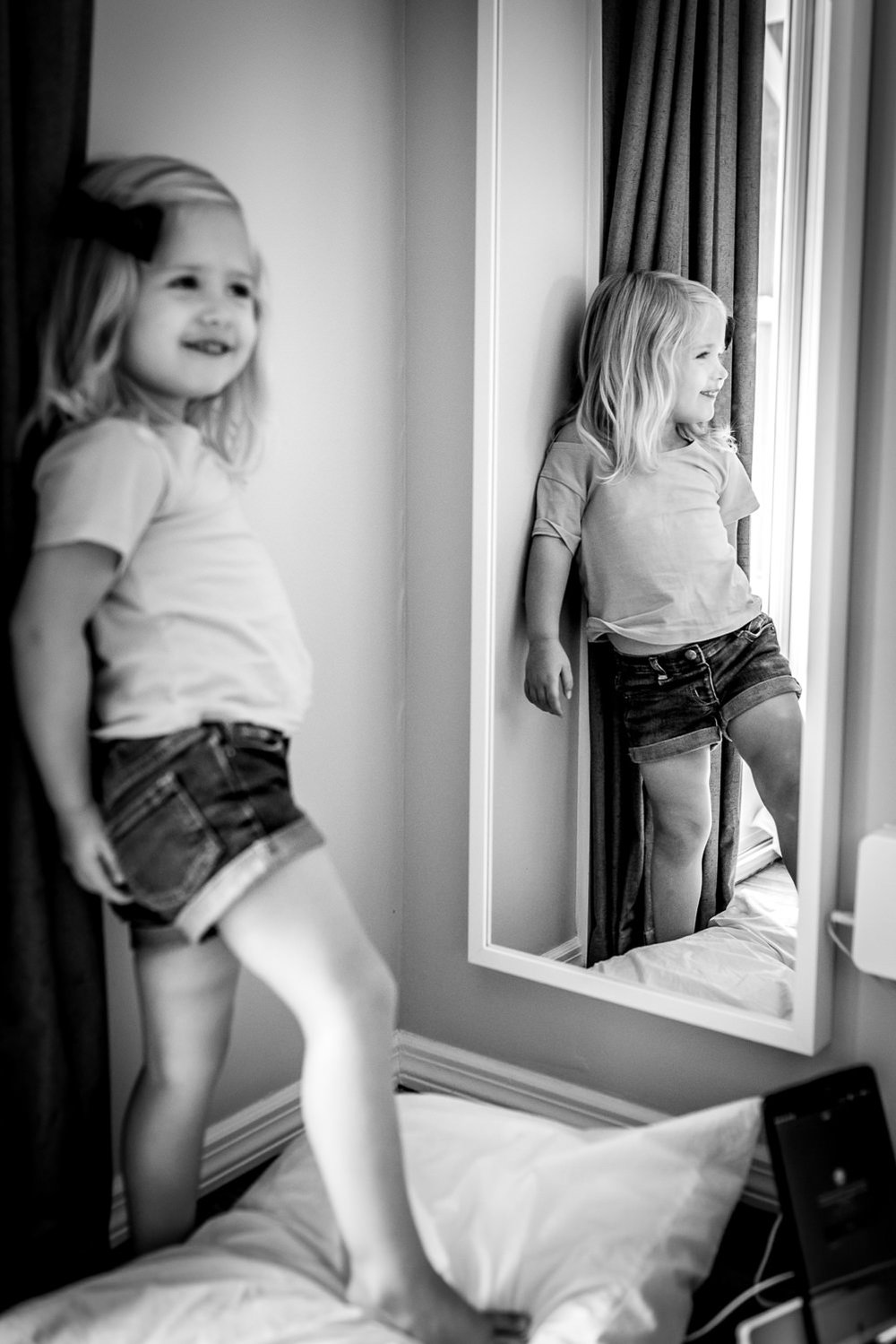 big-sister-smiles-and-makes-faces-in-mirror-at-lifestyle-photo-session