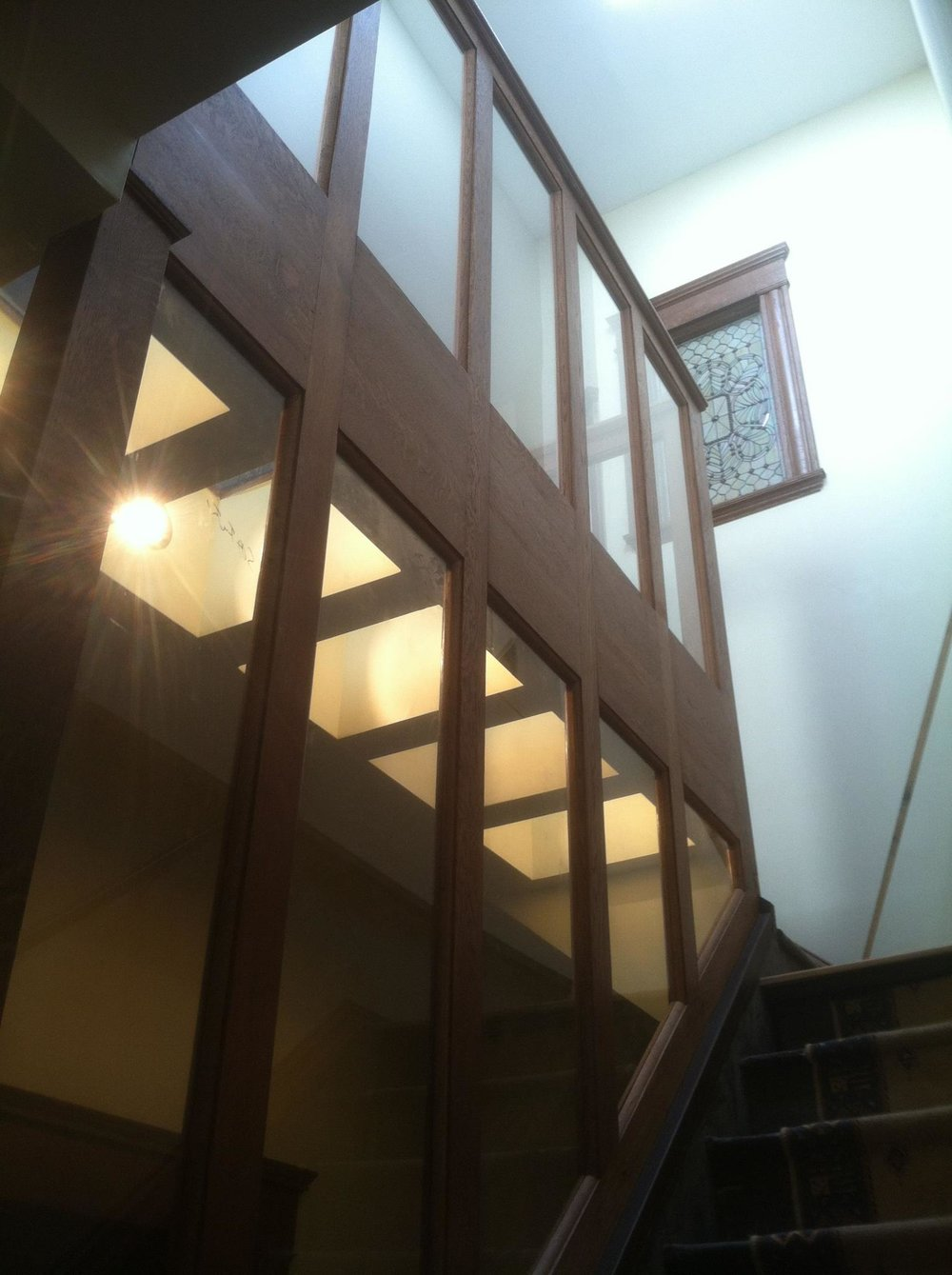 Custom white oak and glass panel stairwell with adjoining glass floor from below. Unique and beautiful!