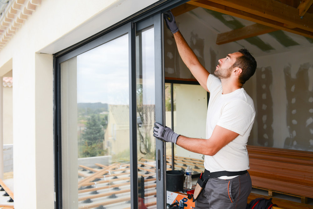 Image of builder fitting sliding doors from Cowboy Builders and how to avoid them