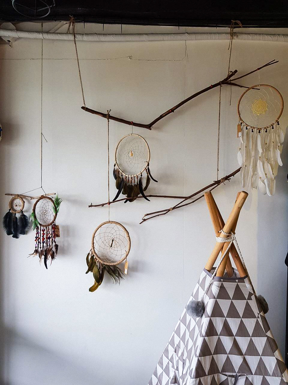 Kamusta? - When you open the door, you'll be greeted by hand-painted signs, a row of dreamcatchers dangling over a grey teepee (similar to what we have at home), and a mix of paper airplanes, crafty mobiles, and lights hanging from the ceiling.