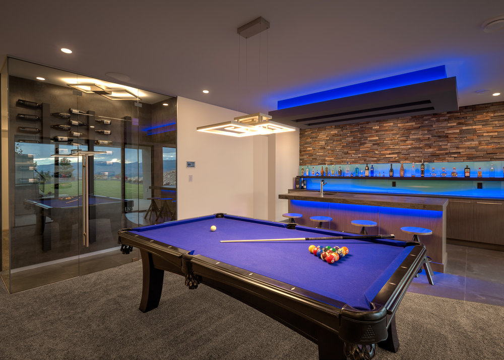 pool table, wine cellar, and bar highlighted with blue lighting