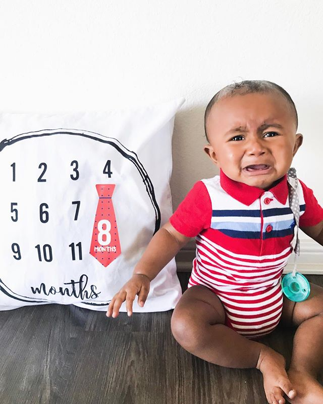 Y'all he was NOT having it today for his milestone pictures 🤦🏾‍♀️ but this little dude is 8 MONTHS OLD!  He smiles and giggles all the time (except for when I don't let him play with his milestone picture sticker 🙄) He's scoots along on the floor and is SO CLOSE to crawling He knows how to wave his hands! @babymummums are still his favorite snack Daniel Tiger is his BFF Loves music and stories Is now a @alvababyusa baby- he is loving his cloth diapers!  Has 1 Bottom Tooth 🙌🏾 We love you Isaiah! ❤️❤️ @batzkids #batzkidslove