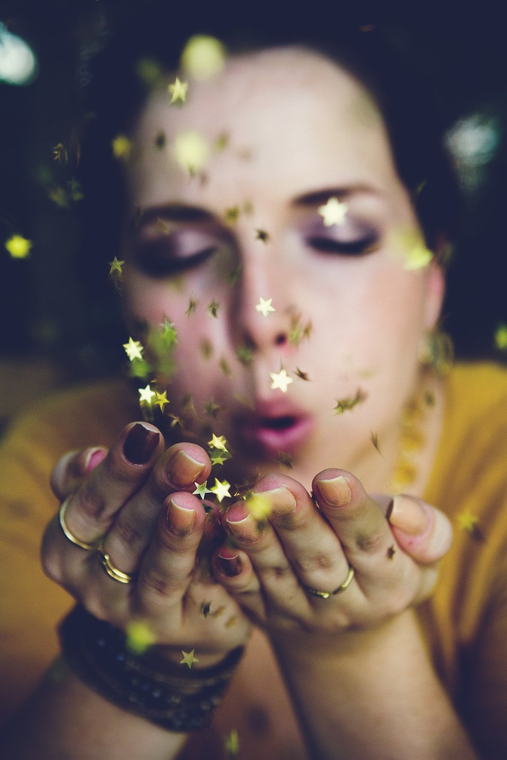 Photo of woman blowing little golden stars out of her open palms.