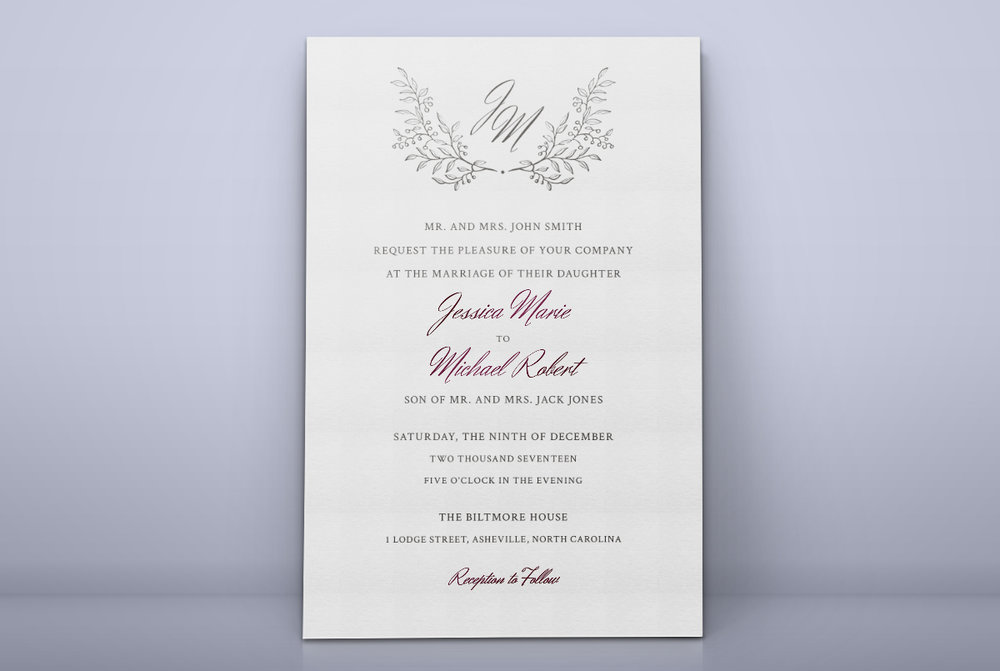 Custom Minimal Classic Charcoal and Burgundy Wedding Invitation with Floral Monogram Standing Against Wall