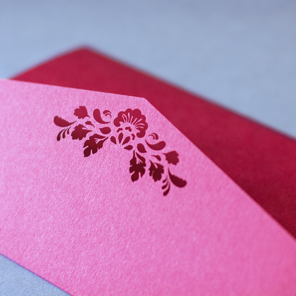 Close-up of custom laser cut trifold pocket burgundy classic invitation floral design on flap