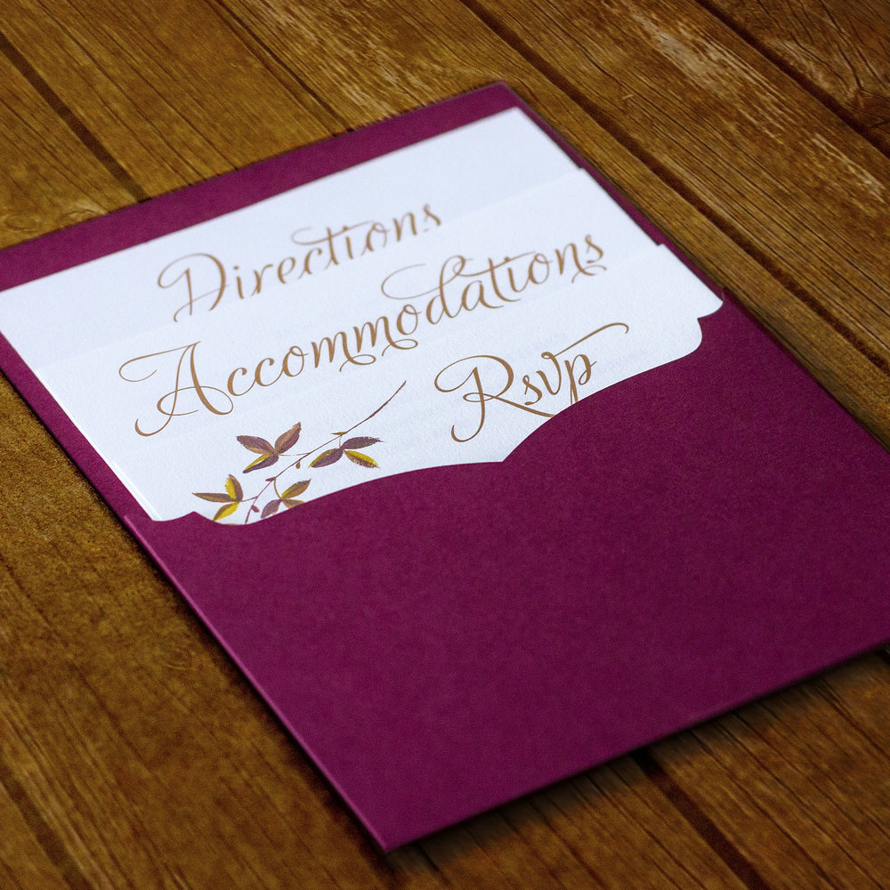 Custom classic script gold and burgundy invitation design with fall floral flourishes, showing back laser cut pocked holding accommodations card, directions card, and RSVP reply card