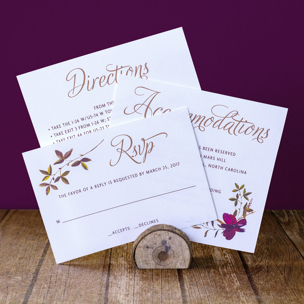 Custom pocket classic script gold and burgundy invitation design with fall floral flourishes, showing accommodations card, directions card, and RSVP reply card