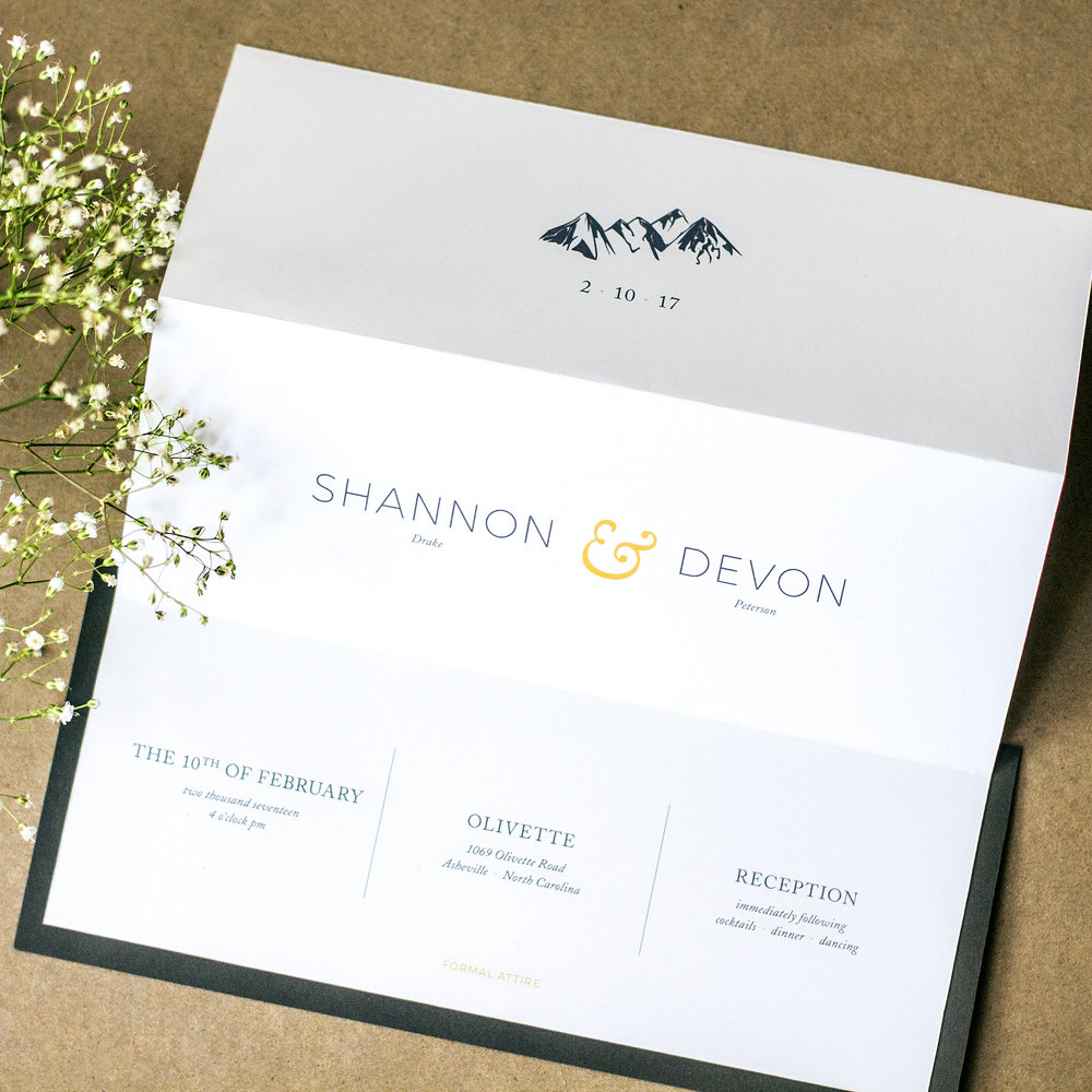Custom Narrow Number Ten Trifold Invitation Charcoal and Gold Modern Minimal Invitation Design with Mountain Illustration next to baby's breath