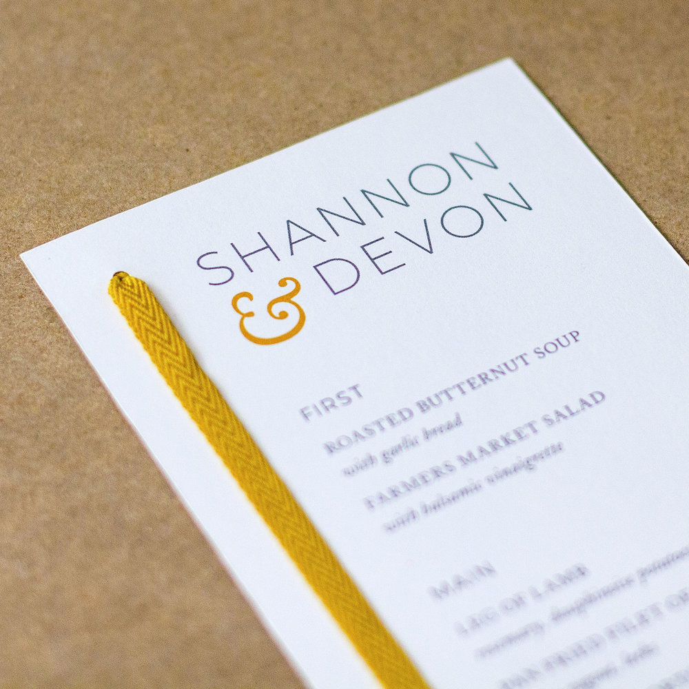 Close-up of Custom charcoal and gold modern menu design with yellow ribbon