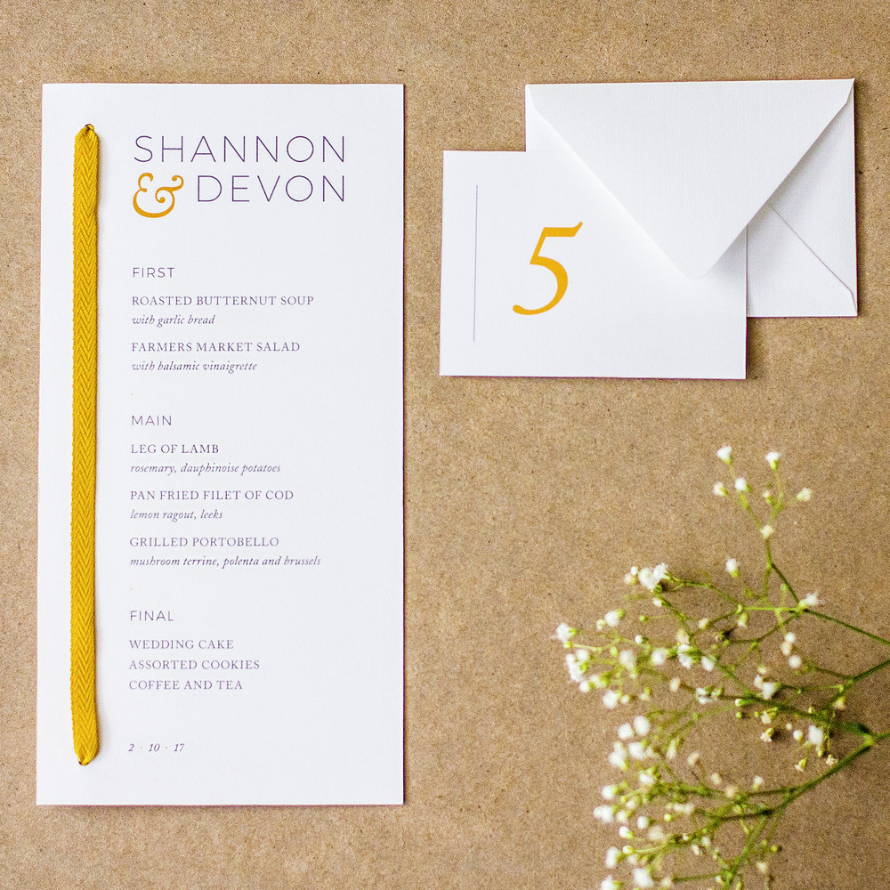Custom charcoal and gold modern menu design with yellow ribbon next to minimal escort card and envelope with baby's breath