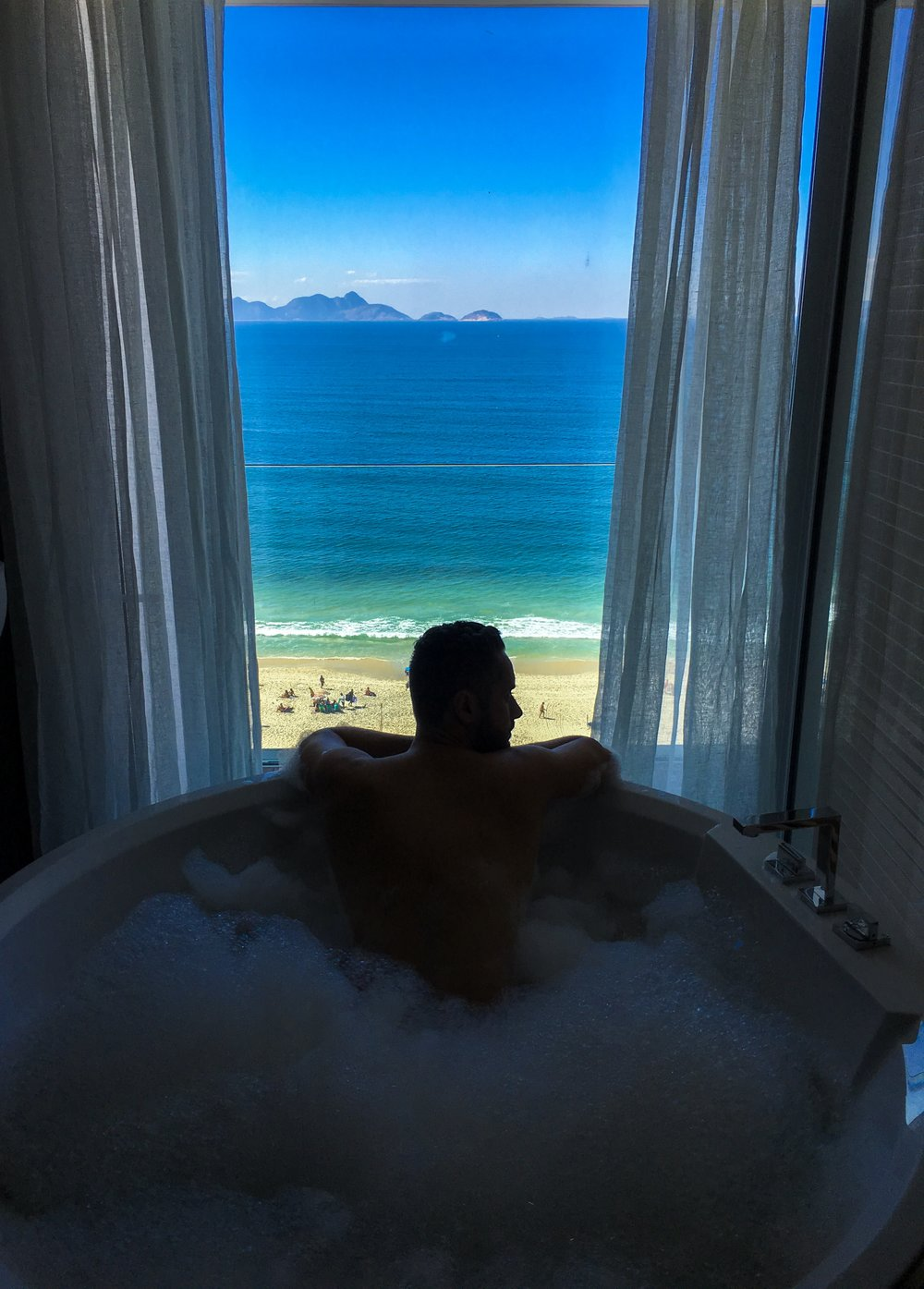As maiores suites do hotel têm banheiras com vista privilegiada da praia.