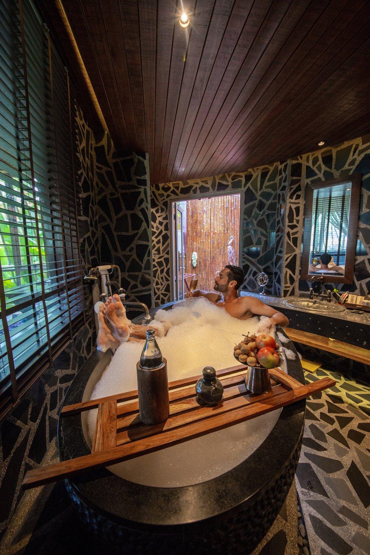 O banheiro da Tree Pool Villa, tem banheira de pedra e chuveiro ao ar livre.
