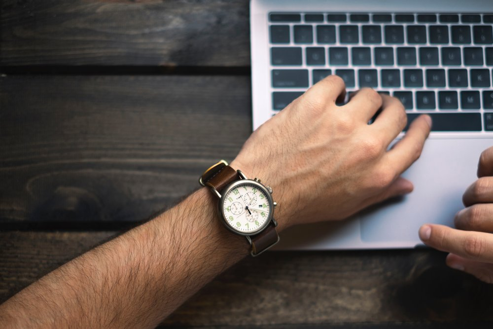 Image of a man wearing a watch and a laptop.