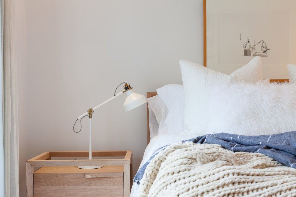 Reading lamp on the side table of a cozy looking bed
