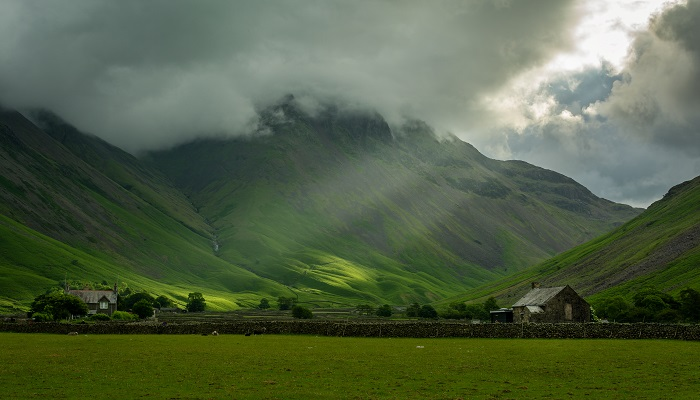 Without the gorgeous beams of light breaking through the clouds this would be a rather unspectacular photograph of a drizzly day by the mountains, but the presence of that light transforms the image.