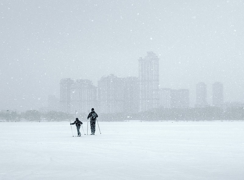 This beautifully simple high-key image keeps the composition simple while drawing attention to the father and his son, the distant city, and the falling snow.