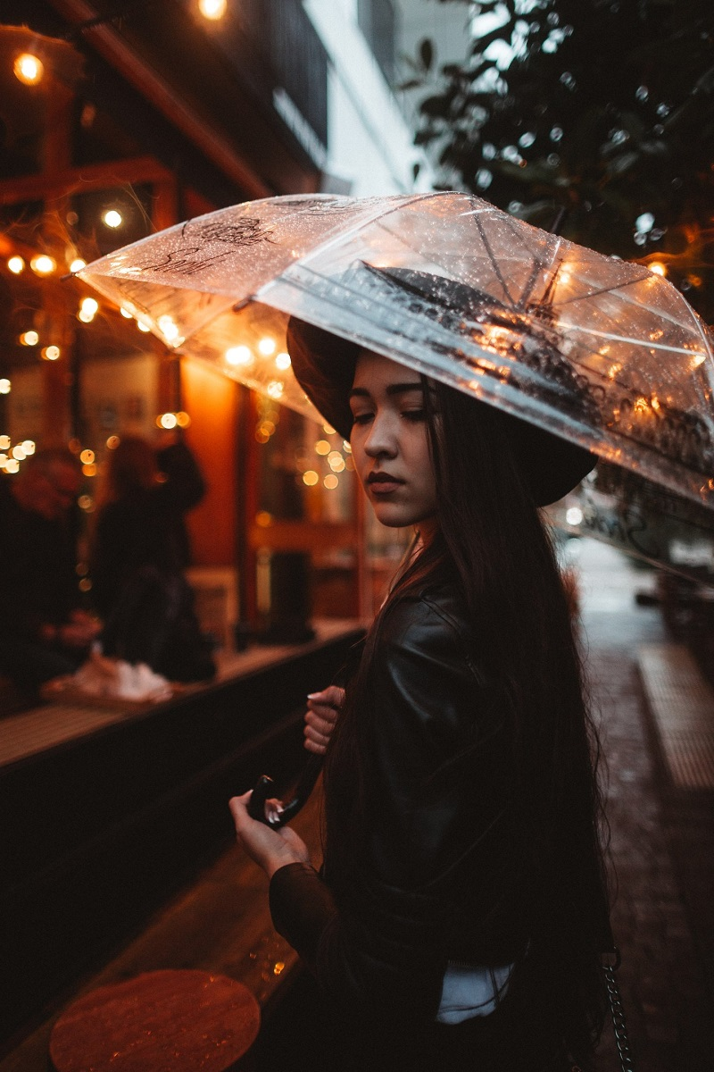 An umbrella can be the perfect compositional aid in the rain. Use it to frame the subject's face and bring the viewer's attention to them.
