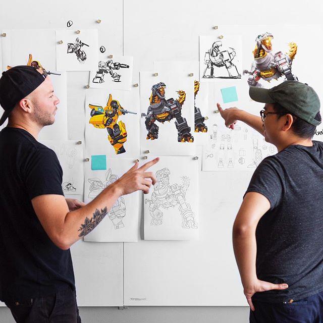 A lot of finger pointing going around here as Tyler and Tony talk Transformers - final art coming soon . . . #transformers #hasbro #pilot #critique #design #designstudio #designinspiration #workinprogress #boston #grimlock #bumblebee #vector #render #illustration #licensingart #styleguide #wip #designlife #illustrator #adobe #sandiegocomiccon #transformerstoys #art #artdirector