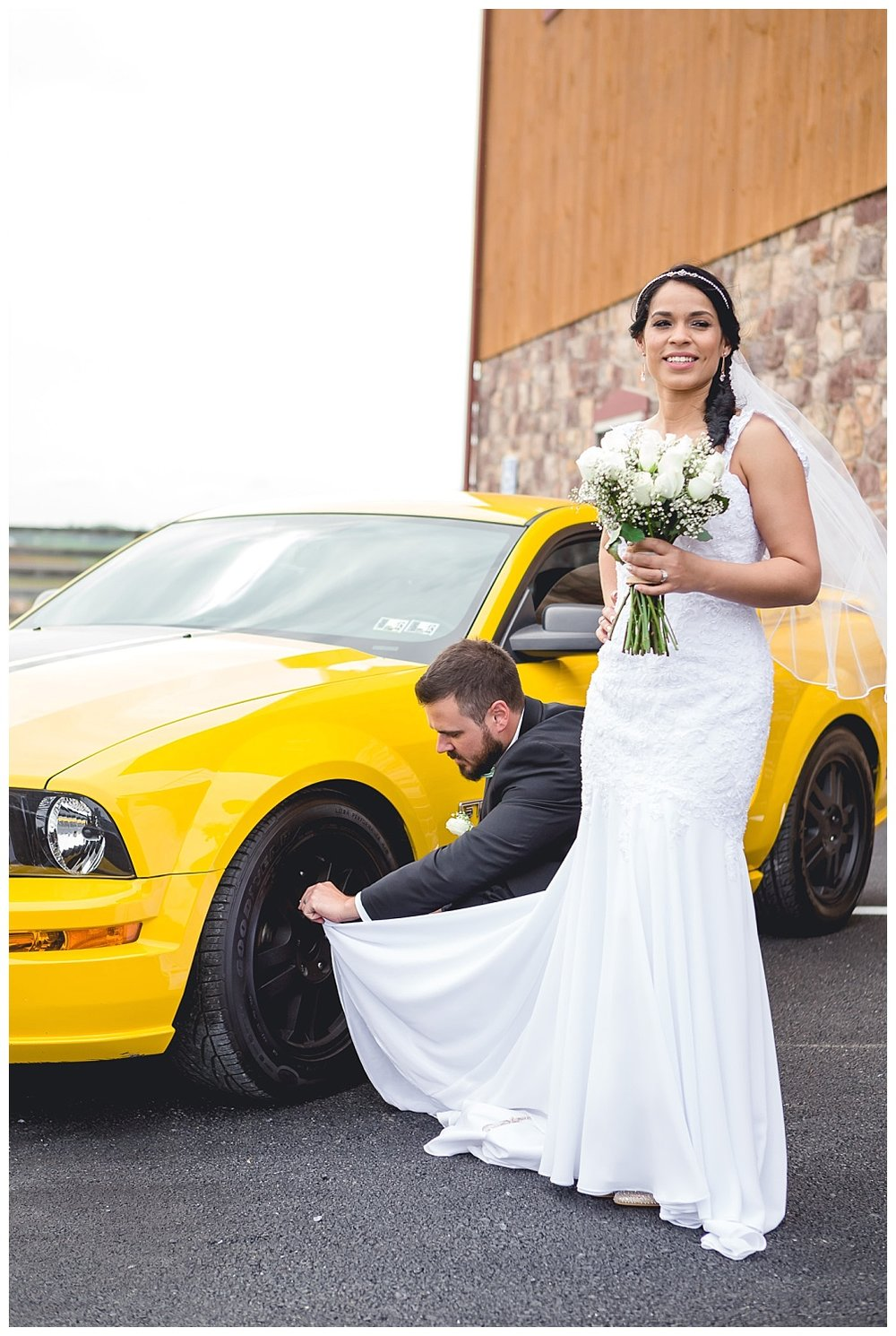 groom cleans mustang wheels with bride's wedding dress
